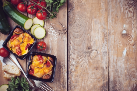 Two dishes of vegetable casserole with cheese, zucchini, cherry tomatoes and oregano on a rustic wooden board with vintage cutlery, food background, home cooking photo