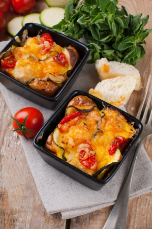 Two dishes of vegetable casserole with cheese, zucchini, cherry tomatoes and oregano on a rustic wooden board with vintage cutlery, home cooking photo