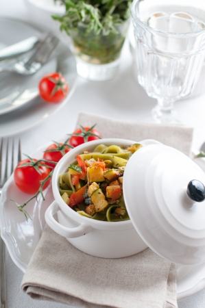 Dietary pasta with spinach, zucchini and cherry tomatoes in a white ceramic pot on served table, fresh homemade lunch. photo