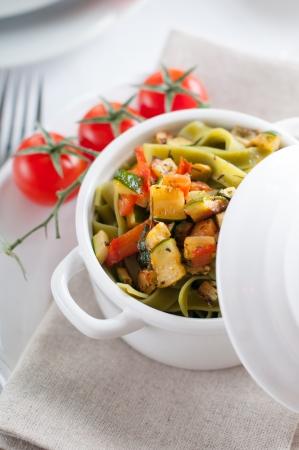 calabacin: Pastas dietéticos con espinacas, calabacín y tomates cherry en una olla de cerámica blanca en la mesa servida, comida fresca hecha en casa. Foto de archivo