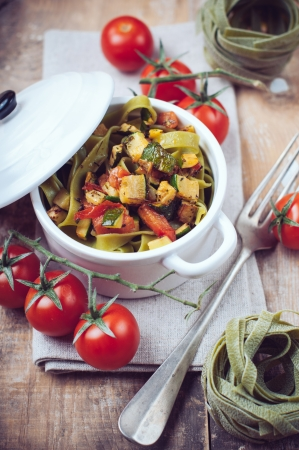 Dietary green pasta with vegetables, spinach, zucchini and cherry tomatoes in a white ceramic pot on a wooden table, fresh rural lunch in a rustic style photo