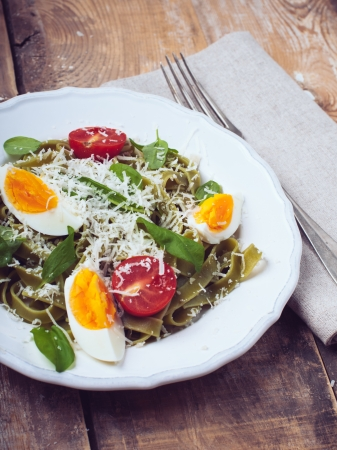 Dietary green pasta with vegetables, spinach leaves, egg, parmesan cheese and cherry tomatoes in a white plate on a wooden table, fresh rural lunch in a rustic style photo