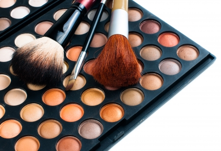 Makeup brushes and eyeshadow palette in beige and orange tones, cosmetics isolated close-up Stock Photo