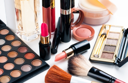 Professional makeup set: eyeshadow palette, lipstick, mascara, blush, powder, make-up brushes and perfume, many cosmetics closeup. Imagens