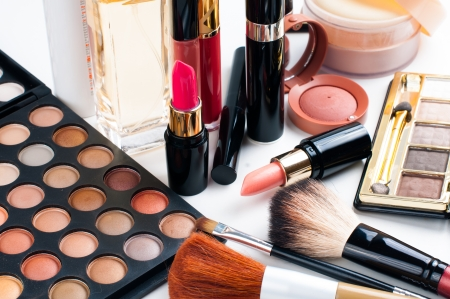 Professional makeup set: eyeshadow palette, lipstick, mascara, blush, powder, make-up brushes and perfume, many cosmetics closeup. photo