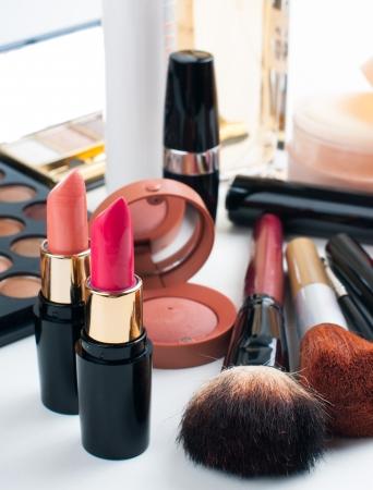 Professional makeup set: eyeshadow palette, lipstick, mascara, blush, powder, make-up brushes and perfume, many cosmetics closeup. photo