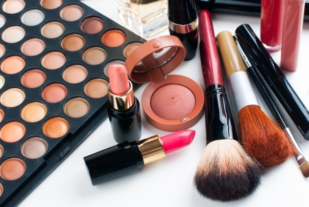 Professional makeup set: eyeshadow palette, lipstick, mascara, blush, powder, make-up brushes and perfume, many cosmetics closeup. Stock Photo