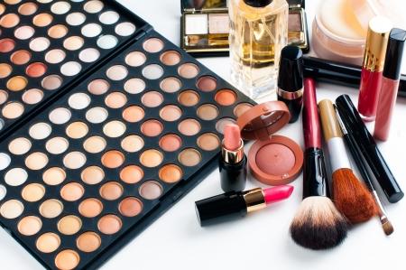 Professionele make-up set: oogschaduw palet, lippenstift, mascara, blush, poeder, make-up kwasten en parfum, veel cosmetica close-up.