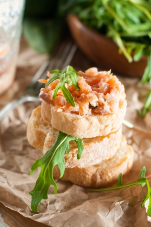 Stack of sandwiches with salmon pate and arugula, fish bruschetta. Rustic homemade Italian cuisine. photo