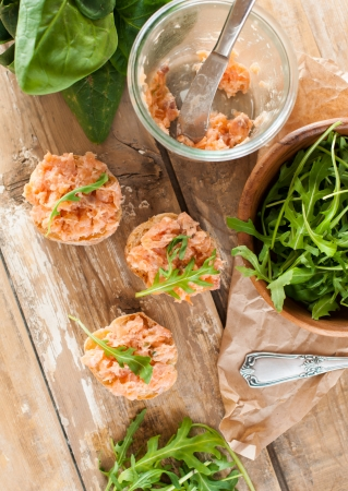 Several sandwiches with salmon pate and arugula, fish bruschetta. Rustic homemade Italian cuisine. photo