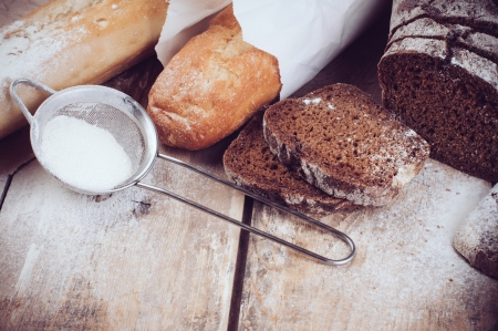 artisan bakery: White french baguette and fresh rustic loaf of wholemeal rye bread, sliced and flour on a wooden board, bakers, food background is. Stock Photo
