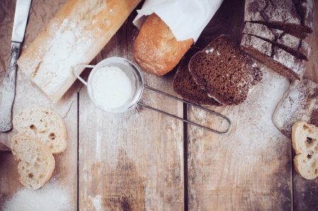 artisan: White french baguette and fresh rustic loaf of wholemeal rye bread, sliced ​​and flour on a wooden board, bakers, food background is.