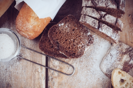 rye bread: White french baguette and fresh rustic loaf of wholemeal rye bread, sliced ​​and flour on a wooden board, bakers, food background is. Stock Photo