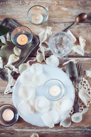 Festive table decor, vintage table setting with rose petals, candles and antique cutlery on a wooden board photo