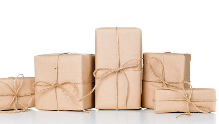 Several gift boxes, postal parcels wrapped in brown kraft paper tied with a rope on a white background, isolated photo
