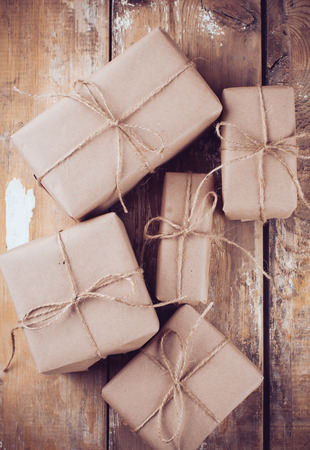 Several gift boxes, postal parcels wrapped in brown kraft paper tied with a rope on a wooden board