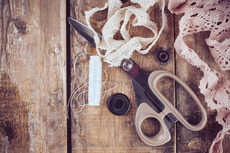 Rustic sewing background: scissors, thread, fabric and lace on an old wooden board, hand-made and crafts, close up photo