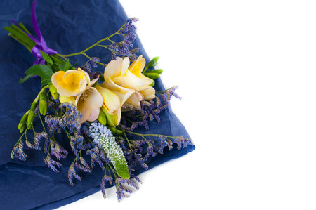Bouquet of yellow and purple flowers and blue wrapping paper on a white background photo