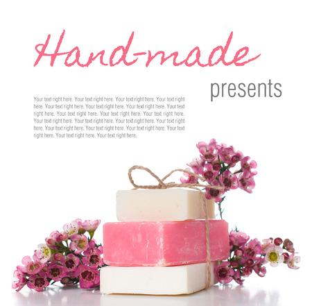 Wit en roze handgemaakte zeep en roze kersenbloesems op een witte achtergrond, geïsoleerd. Geschenken en handgemaakte souvenirs. Stockfoto