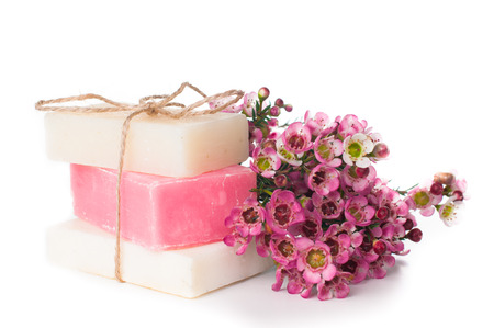 White and pink handmade soap and pink cherry blossoms on a white background, isolated. Gifts and handmade souvenirs.