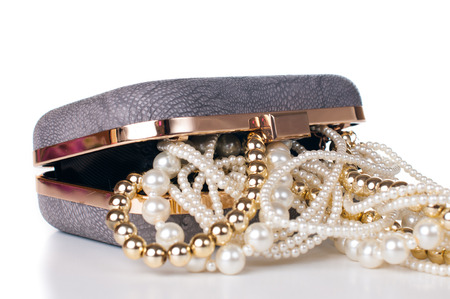 Jewelry of gold and white pearls in the open female handbag on a white background, isolated. photo