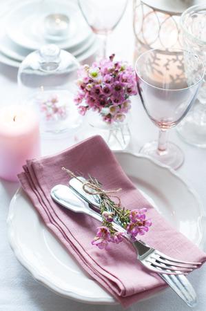 ピンクの花、ナプキン、ビンテージ カトラリー、グラスと蝋燭、明るい夏テーブル装飾とお祝いの結婚式のテーブル。 写真素材