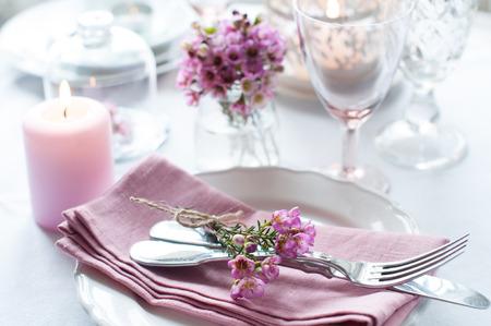 ピンクの花、ナプキン、ヴィンテージ カトラリー、グラスとキャンドル、明るい夏のテーブルの装飾でお祝い結婚式のテーブル。