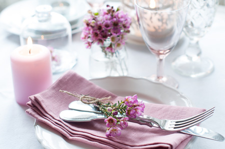 Festive wedding table setting with pink flowers, napkins, vintage cutlery, glasses and candles, bright summer table decor. Фото со стока