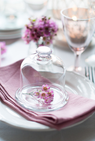Bouquet of pink flowers in a glass bell jar on a festive wedding decorated table, a bright summer table decor. photo