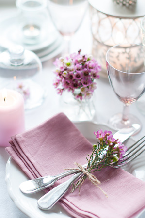 Festive wedding table setting with pink flowers, napkins, vintage cutlery, glasses and candles, bright summer table decor. Standard-Bild