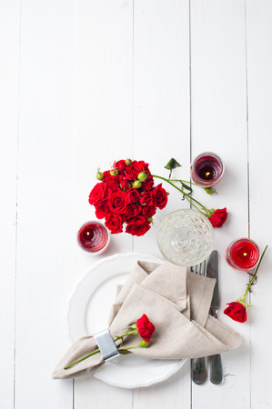 flower arrangement white table: Festive table setting with red roses and candles on white wooden table,  rustic style Stock Photo