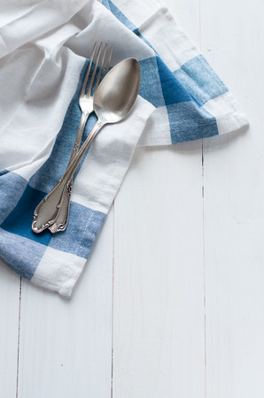 Vintage cutlery and linen napkin on a white wooden board, rustic style photo