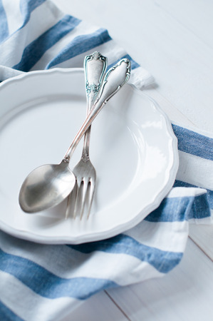 Vintage cutlery, porcelain plate and white linen napkin on wooden board, rustic style photo