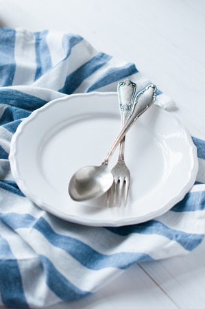 flatware: Vintage cutlery, porcelain plate and white linen napkin on wooden board, rustic style