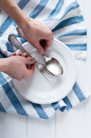 arranging: Male hands arranging cutlery, porcelain plate and white linen napkin on wooden board, rustic style