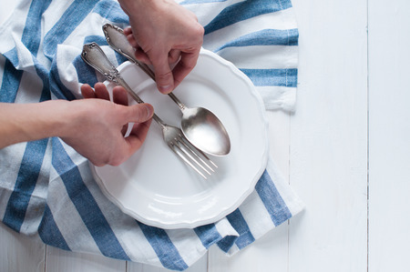 dinnerware: Male hands arranging cutlery, porcelain plate and white linen napkin on wooden board, rustic style