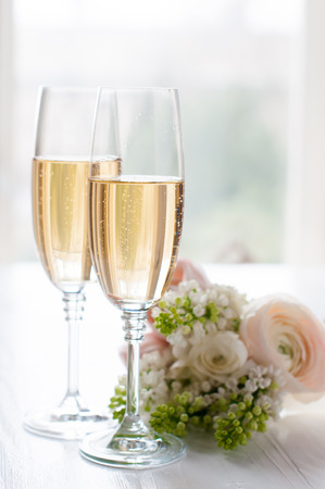 Two glasses of champagne and a beautiful tender festive wedding bouquet of flowers, buttercups and white lilac on a white painted wooden board. Stock Photo - 26356342
