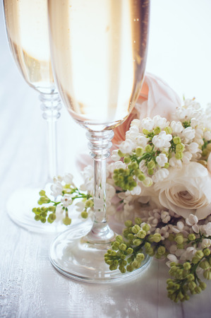 buttercups: Two glasses of champagne and a beautiful tender festive wedding bouquet of flowers, buttercups and white lilac on a white painted wooden board, vintage style Stock Photo