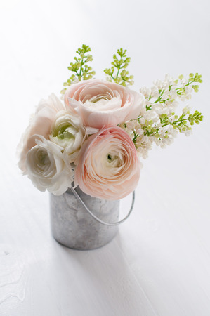 buttercups: Little delicate elegant bouquet of flowers, buttercups and white lilacs in tin can on white wooden table Stock Photo