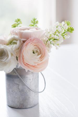 白い木製のテーブル、インテリアにすることができます花、キンポウゲや錫で白いライラックの少し繊細なエレガントなブーケ