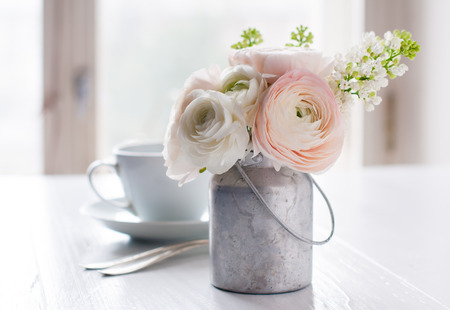 morning: Little delicate elegant bouquet of flowers, buttercups and white lilacs in tin can and a teacup on white wooden table, morning breakfast Stock Photo