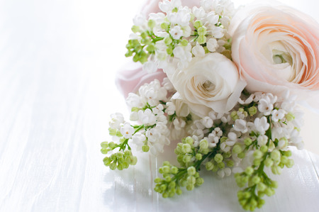 Beautiful delicate festive wedding bouquet of flowers, buttercups and white lilac on a white painted wooden board.