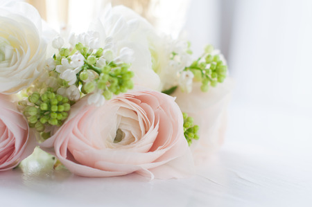 Lovely delicate elegant bouquet of flowers, buttercups and white lilacs, and two glasses of wine on a white painted wooden board, close up
