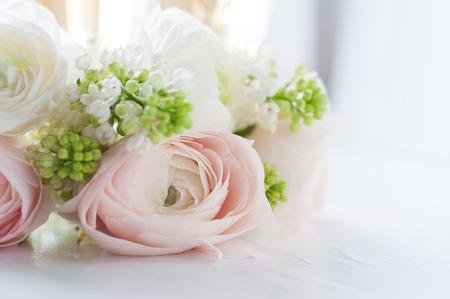 Mooi gevoelig elegant boeket van bloemen, boterbloemen en witte seringen, en twee glazen wijn op een wit geschilderd houten bord, close-up