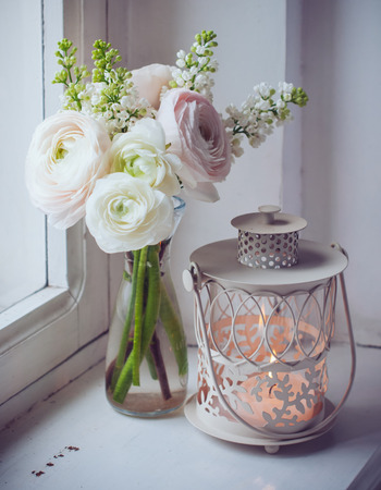 buttercups: Home festive decorations, elegant bouquet of flowers, buttercups and white lilac and candle lantern on white vintage windowsill
