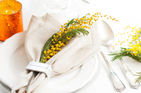 Spring festive dining table setting with yellow mimosa flowers, candles, napkins and vintage cutlery on a white wooden board.