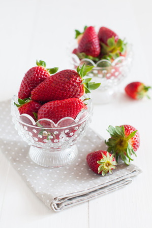 Natural fresh strawberries in a crystal bowl on a wooden board, summer berries, healthy food. photo