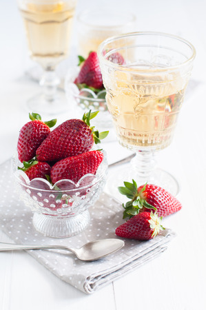 Natural fresh strawberries in a crystal bowl and a few glasses of white wine on a wooden board photo