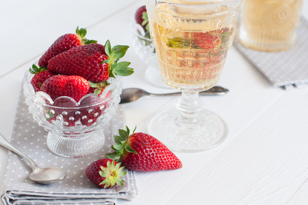 Natural fresh strawberries in a crystal bowl and a few glasses of white wine on a wooden board, drinks and dessert of summer berries. photo