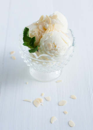 Creamy vanilla ice cream with almonds and mint leaves in a crystal bowl on a white wooden board, sweet summer dessert, homemade food. photo